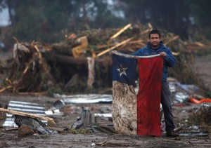 """""""A man holds up a Chilean flag in flooded area alter an earthquake in Pelluhue, some 322 kms. about,200 miles, southwest of Santiago, Suturday, Feb 28. 2010 (AP Photo / Roberto Candia)"""""""